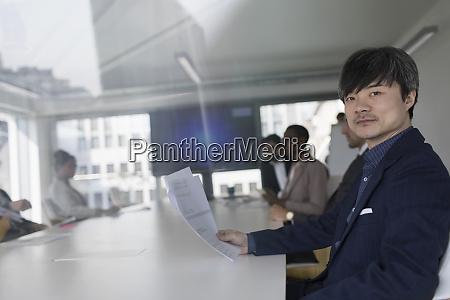 portrait confident businessman reviewing paperwork in