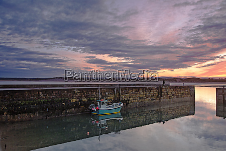 fishing boot moored along jetty wall