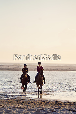 young women horseback riding in ocean