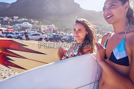 young women with surfboards on sunny