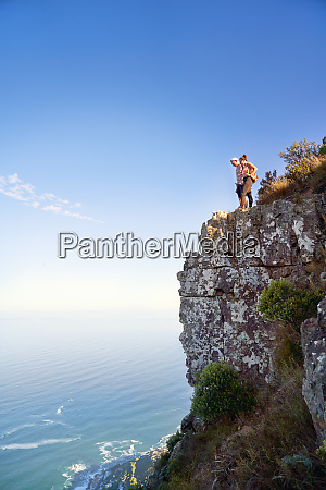 couple on cliff over sunny ocean