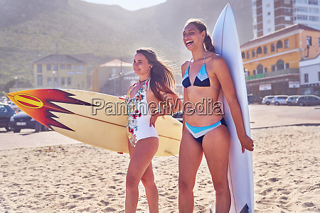 happy young female surfers with surfboards