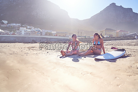 young female surfer friends with surfboards