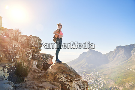 young female hiker on sunny cliff