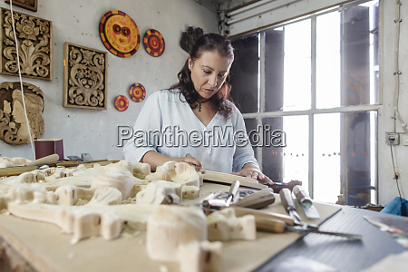woman whittling wood in wood carving