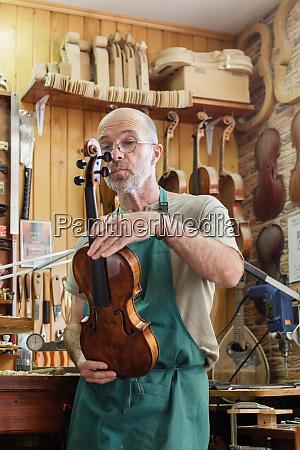 instrument maker in his workshop checking