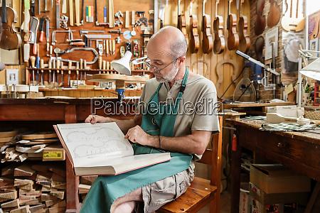 instrument maker reading book on violins
