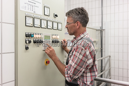 engineer pressing button of control console