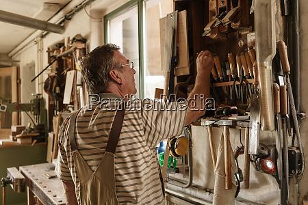 raftsman in wood workshop looking taking