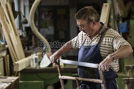 craftsman in his wood workshop adjusting