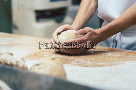 baker forming breads from dough