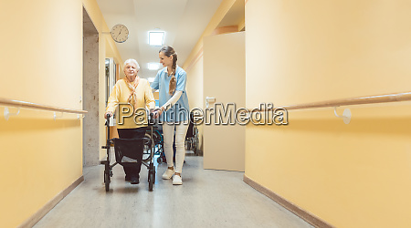 nurse and senior woman walking along