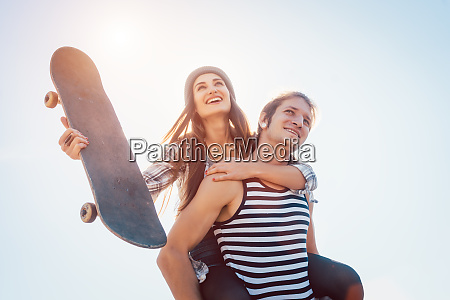 man carrying his girlfriend with skateboard
