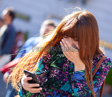young woman laughs looking at mobile