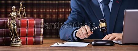 judge striking gavel near mallet and