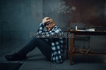 maniac kidnapper sitting on the floor