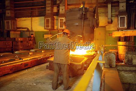 steelmaker pours liquid metal from basket