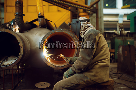 welder works with metal on factory