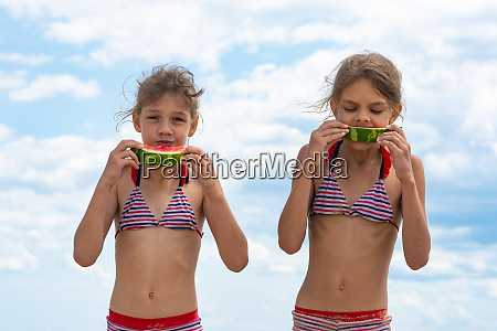 two girls eat watermelon on the