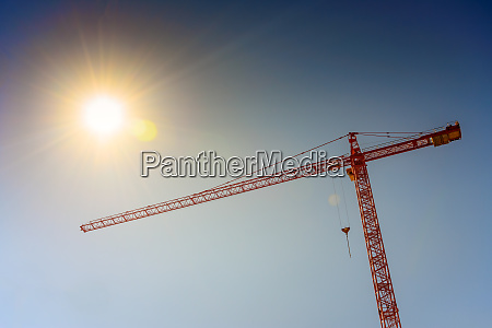 industrial crane and sun on blue