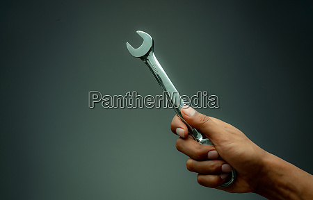 technician hand holding chrome wrench plumber