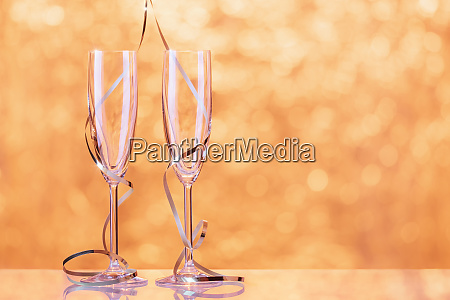 two champagne glasses wrapped with ribbon