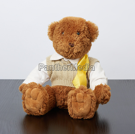 brown teddy bear sits and a