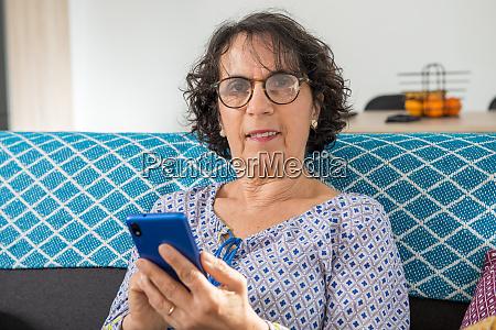 cheerful brunette senior woman using smartphone