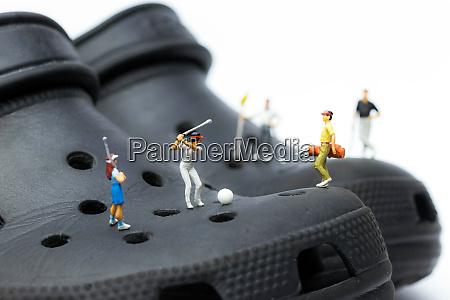 miniature golfers on black shoes