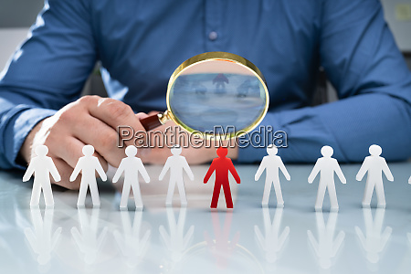 businessperson person holding magnifying glass