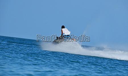 man riding jet ski scooter over