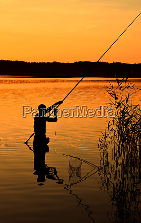 silhouette of man fishing in water