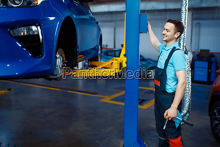 repairman lifts vehicle on car service