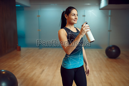 woman drinks water after pilates training