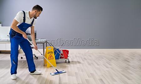 worker mopping floor with wet floor