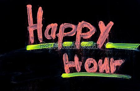 happy hour written on black chalkboard