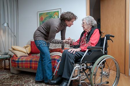 caregiver helping senior woman sitting in