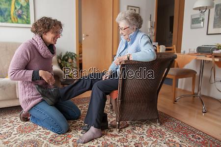 caregiver helping senior putting on her