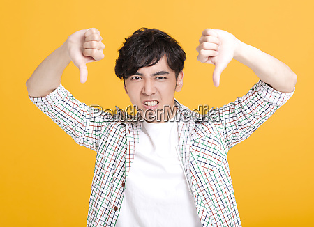 young man showing thumbs down