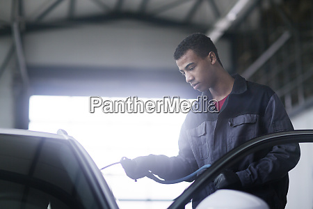 workman fixing car windshield in workshop