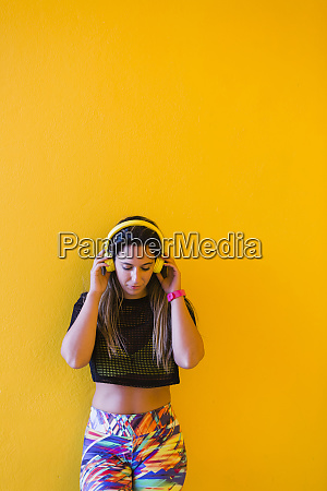 woman wearing headphones by yellow wall