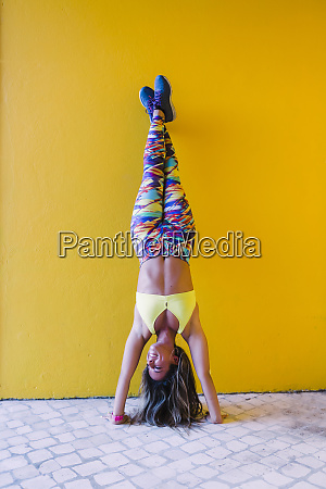 smiling woman doing handstand by yellow