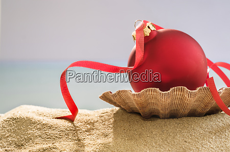 red bauble on shell on sand