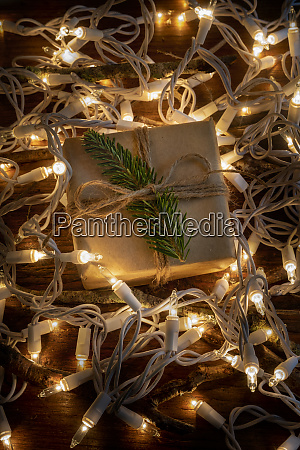christmas present amongst fairy lights