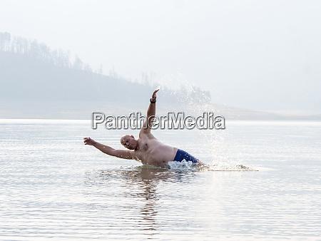 a senior man splashing and swimming