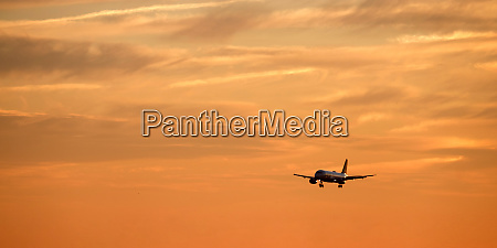 airplane flying in sky at sunset