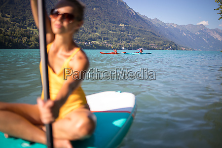 pretty young woman paddling on a
