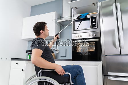 disabled man using grabber tool in