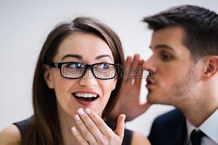 businessman whispering into female partners ear