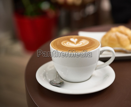 white cup with cappuccino on a